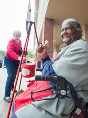 Salvation Army volunteer Alma Crumpton rings her bell Friday, Dec. 22, 2017, as Elti Nebl makes a donation outside of Publix on Cervantes Street in Pensacola.