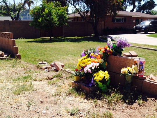 Flowers adorn the central Phoenix wall on April 8 that a car rammed through following a wreck involving teen drivers in late March. The victim, Octavio Grijalva Herrera, died from his injuries.