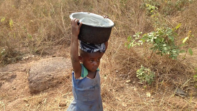 A girl carries water from the well in her Tanzanian village.