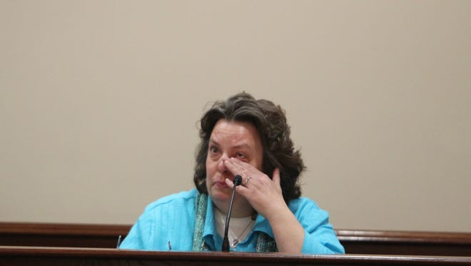 Kelley Hufford wipes her eyes while testifying about her boyfriend's slaying, which is charged with along with two men,.