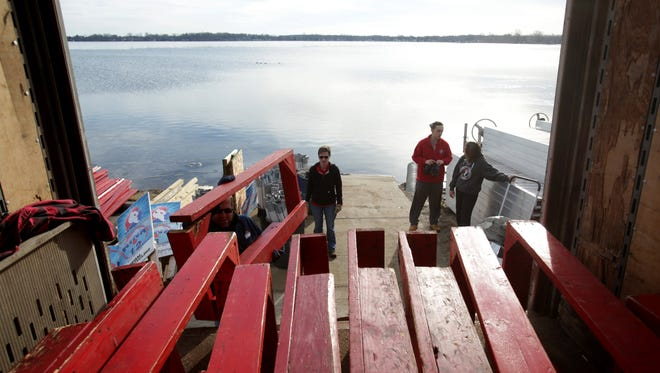 Volunteers move goal boxes into the back of a moving truck at Mac's Marina in Whitmore Lake on Saturday, February 18, 2017. The Michigan Pond Hockey Classic that was to have taken place this weekend on 21 ice rinks was cancelled for the second year in a row due to the warm February weather.