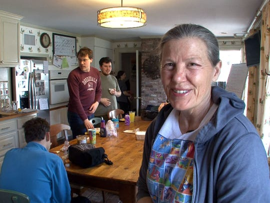 Mai Cleary, President of the Oasis Board of Directors, is interviewed in the kitchen during lunch Tuesday, April 21, 2015.  Participants is the program here learn how to sustain a farm, feed the animals, weave, cook, socialize, and play music at the community for autistic adults.