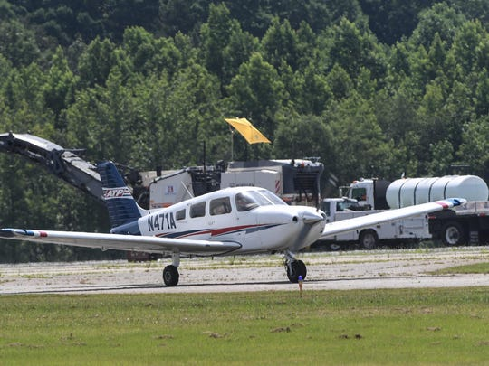 An airplane goes by equipment on another runway area as part of the Anderson Regional Airport runway is closed for asphalt resurfacing by Ashmore Brothers in Anderson.