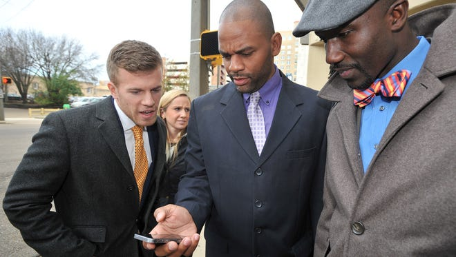 In December 2014, Mayor Tony Yarber, right, and City Councilman De'Keither Stamps, center, get an introduction to the Uber app.