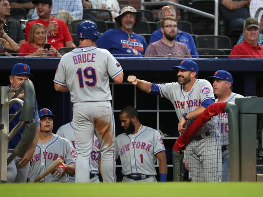 New York Mets right fielder Jay Bruce (19) celebrates a run with manager Mickey Callaway (36) off of a RBI double by first baseman Adrian Gonzalez (not pictured) during the fourth inning against the Atlanta Braves at SunTrust Park.