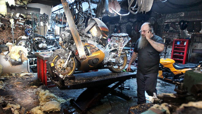 Moses Buresh, owner of D & M Custom Cycle, South Fairmount, walks through the workshop of his business that was damaged by fire late Tuesday.