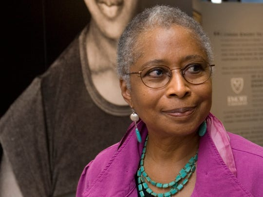 Alice Walker stands in front of a picture of herself