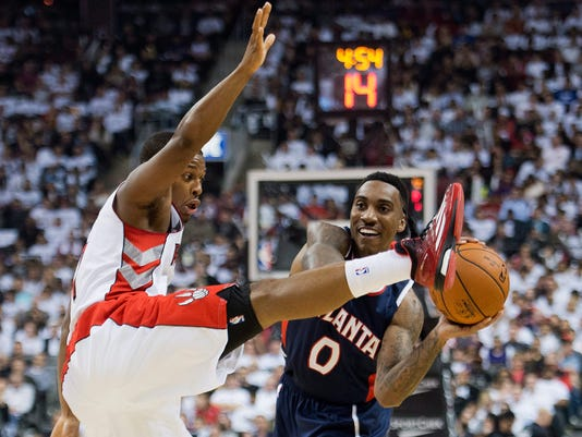 Toronto Raptors guard Kyle Lowry, left, battles for the ball against Atlanta Hawks guard Jeff Teague, right, during first half of an NBA basketball game in Toronto on Wednesday, Oct. 29, 2014. (AP Photo/The Canadian Press, Nathan Denette)