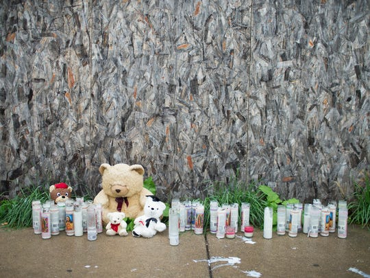 A makeshift memorial is shown along the sidewalk in