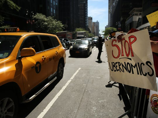 New York City taxi drivers hold a rally in front of Governor Andrew Cuomo's office to protest against recent inroads made by the Uber car service on Sept 16, 2015, in New York City.