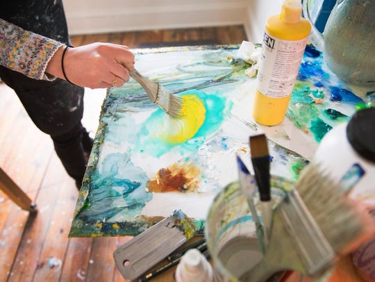 Kiah Ann Bellows mixes paint in her studio space at
