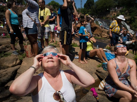 Carla Brundage of Madison, NJ looks up at the solar eclipse in Falls Park in downtown Greenville on Monday, August 21, 2017.
