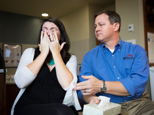 Brent Watkins hands a tissue to his wife, Natalie,