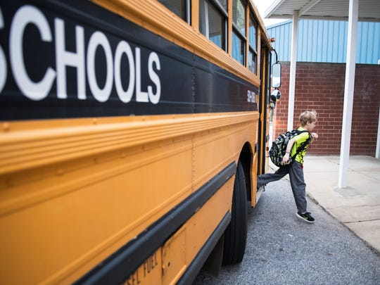 A student gets off the bus at Fork Shoals Elementary