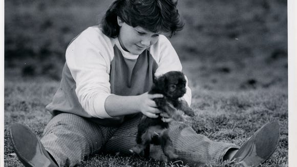 Crystal Kitts, 13, gets to know her new 7-week-old puppy during a sunny day in January of 1986.