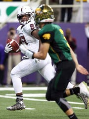 Atlias Bell of Dowling Catholic scoops up a fumble and scores a touchdown against Cedar Rapids Kennedy in the Class 4A Championship game Monday, Nov. 23, 2015.