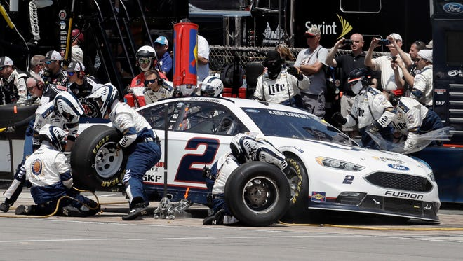 Crew members work on the car of Brad Keselowski during a pit stop Monday at Pocono Raceway.