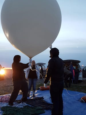 Students from the Great Falls College MSU STEM Club prepare to launch a high-altitude balloon at the Choteau Airport.