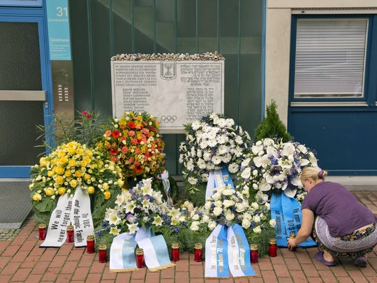 A woman lights candles in front of wreaths at a memorial at the former accommodation building of the Israeli Olympic team in Munich on Sept. 5, 2012, during a commemoration ceremony for the assassination victims of the Olympic games in Munich in 1972. Seventeen people died in a failed liberation attempt of Israeli hostages, 11 of them of Israel's Olympic team, five terrorists and a German police officer.