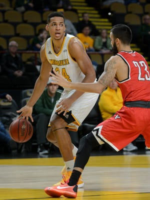 UW-Milwaukee forward Bryce Nze looks to pass while guarded by Youngstown State guard Francisco Santiago.