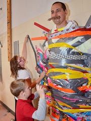 Colorado Elementary School students Gracie Reimers and Rhys Boynton add strips of duct tape to help stick Principal Ryan Castle to the gymnasium wall on Oct. 17 in Muscatine. Castle challenged the students to sell 10,000 tickets for the school's annual fall festival Oct. 10 with the reward of being able to duct tape him to the wall and let him hang there through lunch.