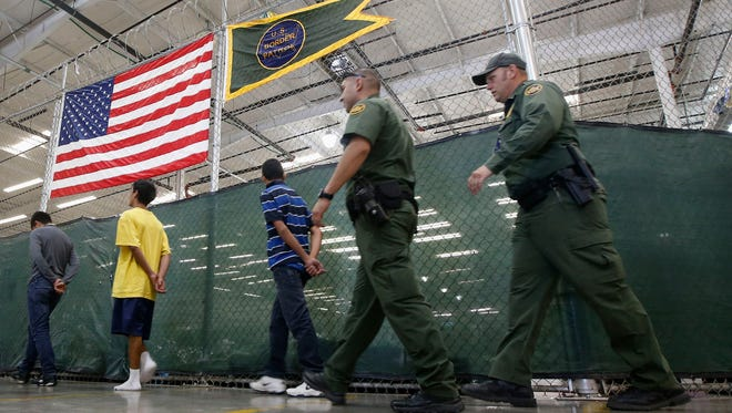 Young detainees are escorted to an area to make phone calls as Central American immigrant children are processed and held in Nogales, Ariz.