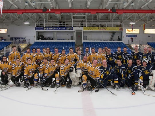 Posing after the charity game at USA Hockey Arena are players for Schoolcraft College and the Michigan State Police.