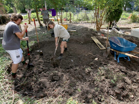 From left, Ian Bernstein of Ann Arbor and Julia Liggett of Pontiac work for Creating Sustainable Landscapes and they are creating a rain garden at the Detroit home of Nicola Binns on Wednesday, August 9, 2017.