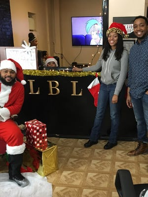 De'Jahn Ruffin, dressed as Santa Claus, left to right, Satara Brown, founder of Rebuilding Our Children and Community, and Vince Ross, owner of Laced Barber Lounge, are shown during the Dec. 22 holiday event at the city shop.