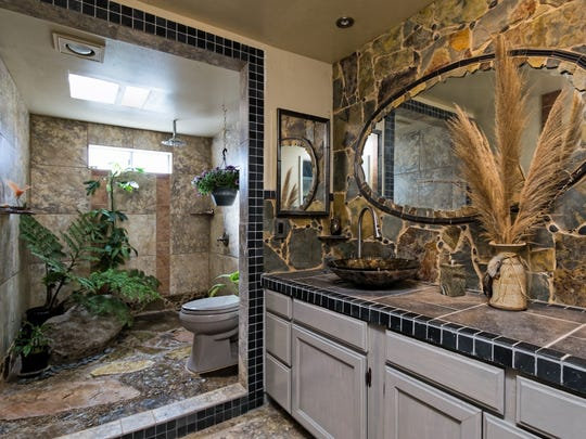The third-floor master suite of this Panama Drive home in Oxnard features a master bath with an large shower complete with natural rock planters, live tropical plants and a rain shower head.