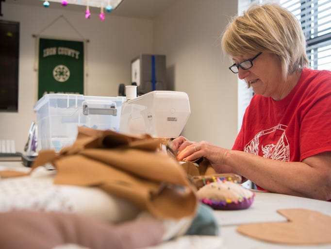 Cheryl Williams sews a 'procedure doll' for children