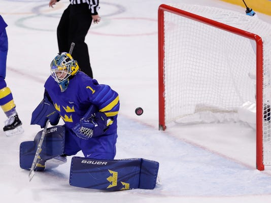 The puck shot by Ayaka Toko (4), of Japan, gets past goalie Sara Grahn (1), of Sweden, for a goal during the overtime period of the classification round of the women's hockey game at the 2018 Winter Olympics in Gangneung, South Korea, Sunday, Feb. 18, 2018. Japan won 2-1. (AP Photo/Frank Franklin II)