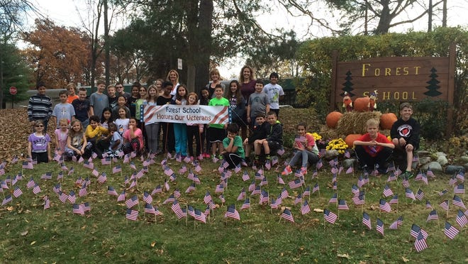 Forest Elementary's student council and staff show off the U.S. flag display outside their school.