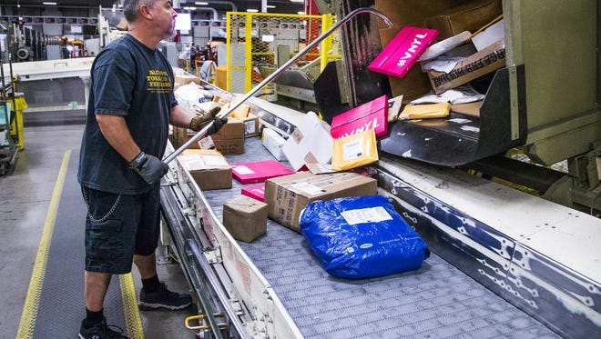 Mail handler John Arnott sorts packages at a dumping station at the U.S. Postal Service West Valley Processing and Distribution Center in Phoenix on Dec. 6, 2016.  The Christmas rush of mail is beginning to ramp up.
