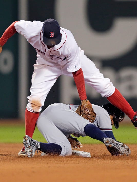 Boston Red Sox shortstop Xander Bogaerts, top, makes the tag as Atlanta Braves' Mallex Smith lifts off second base, while over-sliding the bag on a steal, during the sixth inning of a baseball game at Fenway Park in Boston, Thursday, April 28, 2016. Smith was initially credited with the stolen base, but reversed after a videotape review. (AP Photo/Charles Krupa)