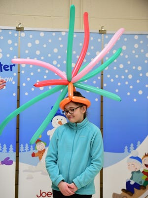 Mackenzie Cooper of Redford is thrilled as she wears the balloon hat during the Family Fun Night last week.