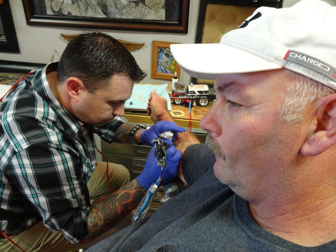 Client David Hearn prefers not to watch as tattoo artist