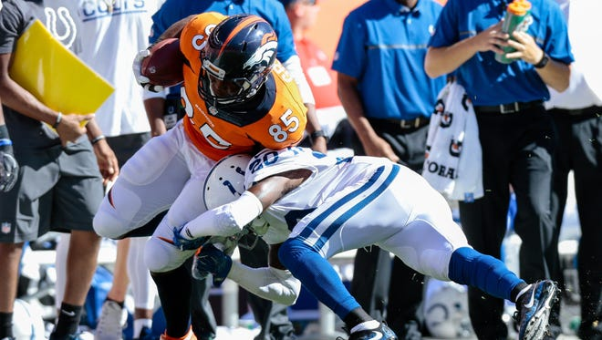Broncos tight end Virgil Green is tackled by Colts cornerback Darius Butler during their game Sunday.