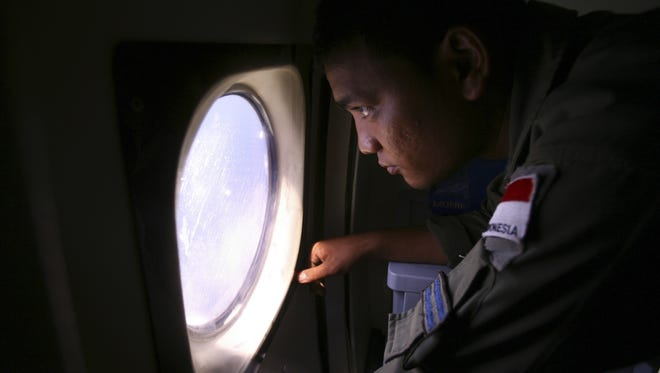FILE - In this March 10, 2014 file photo, an Indonesian Navy crew member scans the water bordering Indonesia, Malaysia and Thailand during a search operation for the missing Malaysian Airlines Boeing 777 near the Malacca straits.