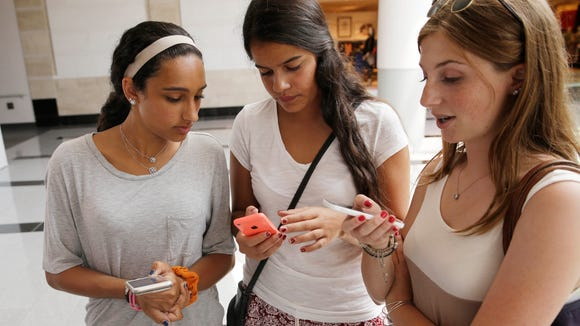In this July 27, 2015, photo, teenagers check their phones at Roosevelt Field shopping mall in Garden City, N.Y.