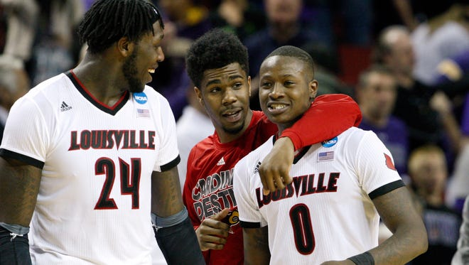 U of L's Terry Rozier, #0, right, celebrates with teammates Anton Gill, #1, center, and Montrezl Harrell, #24, after Rozier forced a UC Irvine turnover in the closing seconds of U of L's win at the KeyArena in Seattle during the second round of the NCAA tournament.