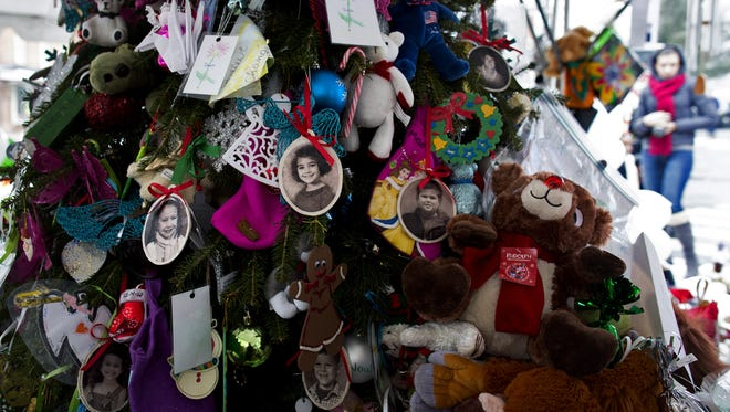 Portraits of slain students and teachers hang from a tree at a memorial in Newtown, Connecticut.