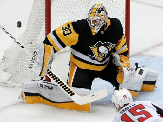 FILE - In this Feb. 13, 2018, file photo, Pittsburgh Penguins goaltender Matt Murray blocks a shot during an NHL hockey game against the Ottawa Senators in Pittsburgh. Matt Murray looks ready to return from a concussion that's kept him out for the last three weeks. Murray practiced with his teammates on Monday, March 19, 2018, and could be available on Tuesday night when the two-time defending Stanley Cup champions visit the New York Islanders. (AP Photo/Gene J. Puskar, File)