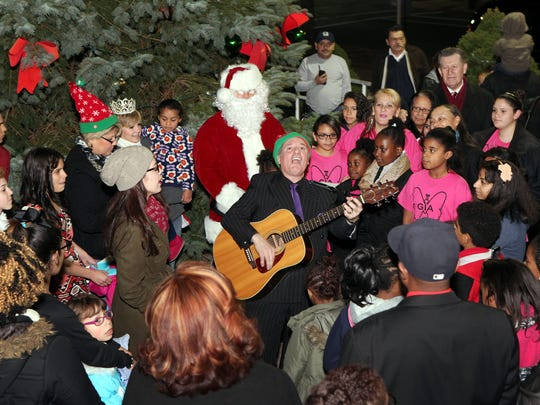 """Vineland Mayor Ruben Bermudez plays guitar and leads the crowd in singing """"Feliz Navidad"""" outside City Hall during a tree lighting ceremony Sunday evening."""
