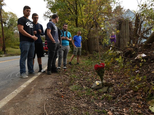 A group of Roy C. Ketcham students gathers around a memorial on the side of Old Hopewell Road in the Town of Wappinger.
