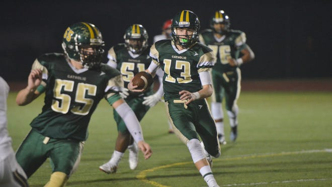 Melbourne Central Catholic quarterback Joaquin Collazo runs with a convoy of teammates during the Hustlers' win over Cardinal Mooney on Friday night.