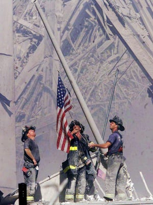 Firefighters raise a flag on the afternoon of Sept. 11, 2001, in the wreckage of the World Trade Center towers in New York following terrorist attacks that brought down the towers.