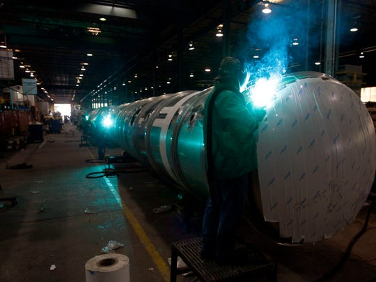 A worker welds support ribs onto the side of a tanker truck being built at Paul Mueller Company in October 2013.
