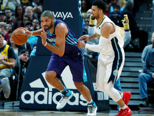 Charlotte Hornets guard Nicolas Batum, left, picks up a loose ball as Denver Nuggets guard Jamal Murray in the first half of an NBA basketball game Monday, Feb. 5, 2018, in Denver. (AP Photo/David Zalubowski)