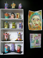 Dawna Magliacano's 'Tubers' are characters sculpted around discarded toilet paper rolls, set on a shelf next to some of her whimsical illustrations.